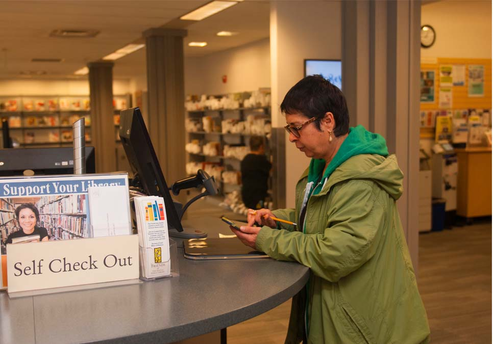 Library patron at self-checkout station at the Rainier Beach Branch